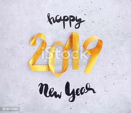 istock New Year greeting card with glowing golden paper numbers 2019 923010082