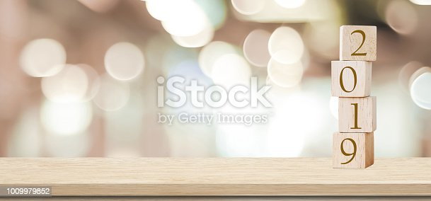 istock 2019 new year greeting card, wooden cubes with 2019 on wood table over blur bokeh background with copy space for text, new year template 1009979852