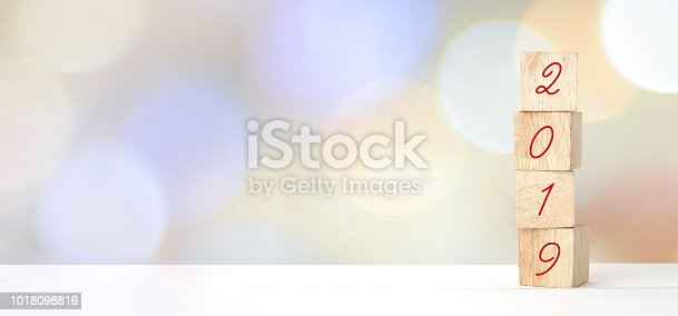 1009979852 istock photo 2019 new year greeting card, wooden cubes with 2019 on wood table over blur bokeh background with copy space for text, new year template 1018098816