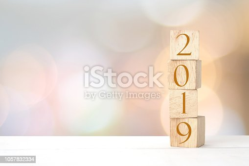 1009979852 istock photo 2019 new year greeting card, wooden cubes with 2019 on wood table over blur bokeh background with copy space for text, new year template 1057832334