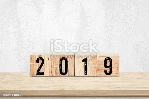 1009979852 istock photo 2019 new year greeting card, wooden cubes with 2019 on wood table over white wall background 1002111806