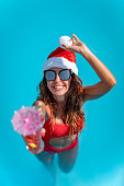 Young beautiful woman in the swimming pool in Santa Claus hat celebrating New Year and Christmas in hot country with glass of cocktail.