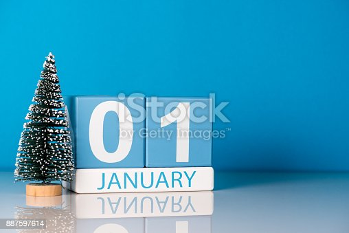 945046208 istock photo New year. January 1st. Day 1 of december month, calendar with little christmas tree on blue background. Winter time. Empty space for text. New year concept 887597614