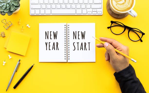 nuevo año nuevo texto de inicio con el joven escribiendo en el bloc de notas en la mesa de escritorio de color. conceptos de objetivo-acción y resolución de objetivos de negocio - año nuevo fotografías e imágenes de stock