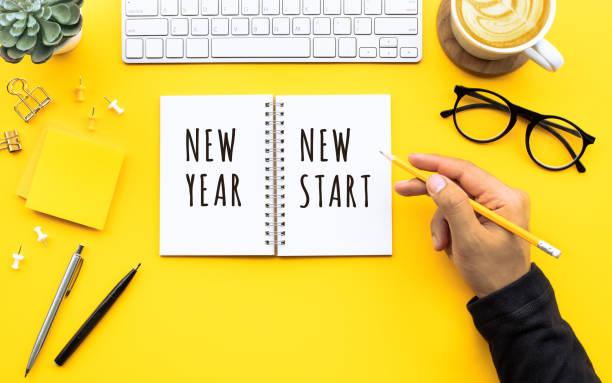 new year new start text with youngman writing on notepad on color desk table.business goal-plan-action and resolution concepts - new year imagens e fotografias de stock