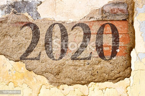 istock 2020 new year painted on  Old Brick Wall Texture. Painted Distressed Wall Surface. Grungy Wide Brick wall. Grunge Red Stonewall Background. Shabby Building Facade With Damaged Plaster. 1073803310