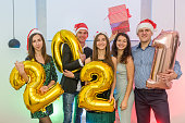 istock New year party. Happy company of men and women with golden air balloons celebrating 1194449585