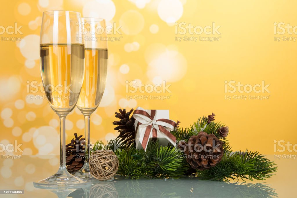 New Year pine branch with cones, gift and wine glasses with champagne, on yellow background stock photo