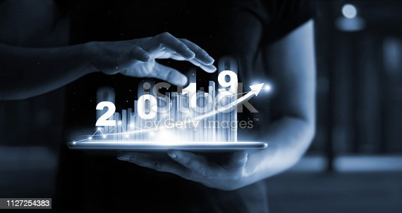 istock 2019 New year planning business and financial concept. Businessman using tablet analyzing sales data and economic growth graph chart 2019. E-commerce and network, Business strategy. Digital marketing on blue background. 1127254383