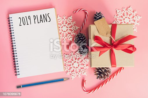 istock 2019 New Year Plans, top view brown gift box, notebook and christmas decoration for new year on pink pastel color. 1076095678