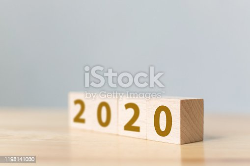 1066508880 istock photo New year resolution 2020 concept. Wooden block cube with year number on table 1198141030