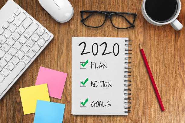 new year resolution goal list 2020 - business office desk with notebook written in handwriting about plan listing of new year goals and resolutions setting. - new years day stock pictures, royalty-free photos & images