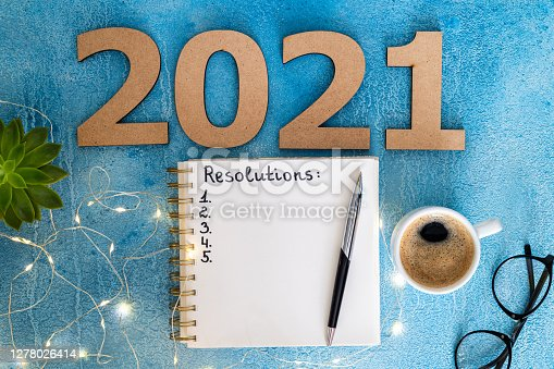 New year resolutions 2021 on desk. 2021 goals with notebook, coffee cup and eyeglasses on blue background. Goal, plan, strategy, action, idea concept. Copy space