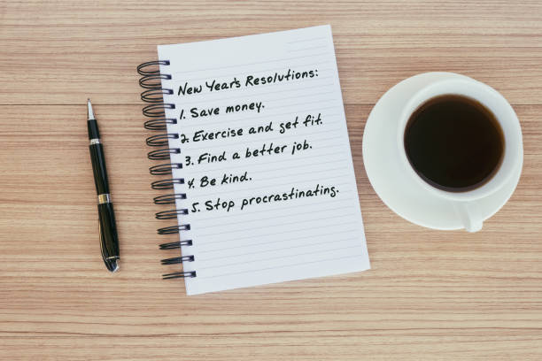 New Year Resolutions List on Notepad on Top of Wood Desk stock photo