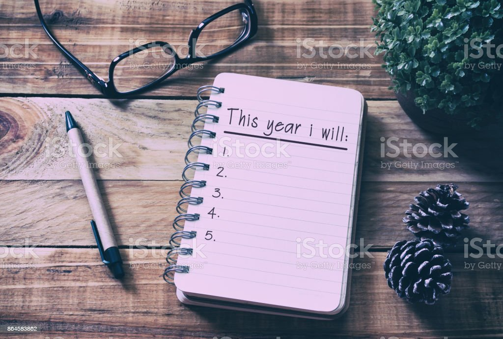 New Year Resolutions List on Notepad on Top of Wood Desk royalty-free stock photo