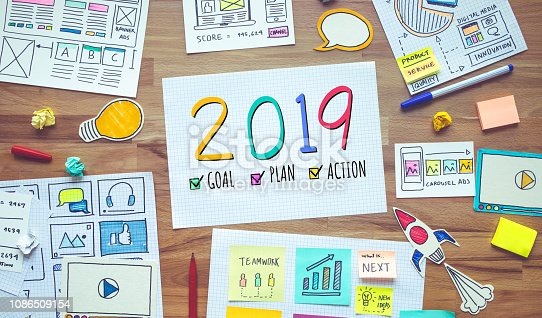 istock 2019 new year resolutions with business digital marketing and paperwork sketch on wood table.analysis strategy concepts 1086509154