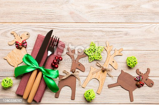 New year set of fork and knife on napkin. Top view of christmas decorations and reindeer on wooden background. Holiday family dinner concept with empty space for your design.