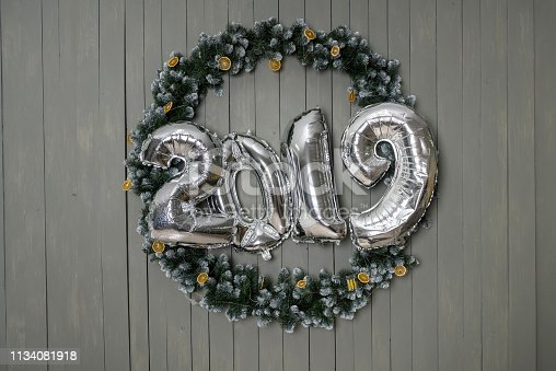 1043435102 istock photo 2019 new year - silfer foil ballon in wooden background 1134081918