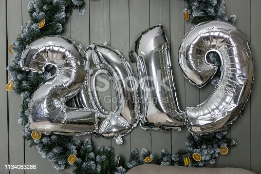 1043435102 istock photo 2019 new year - silfer foil ballon in wooden background 1134083268