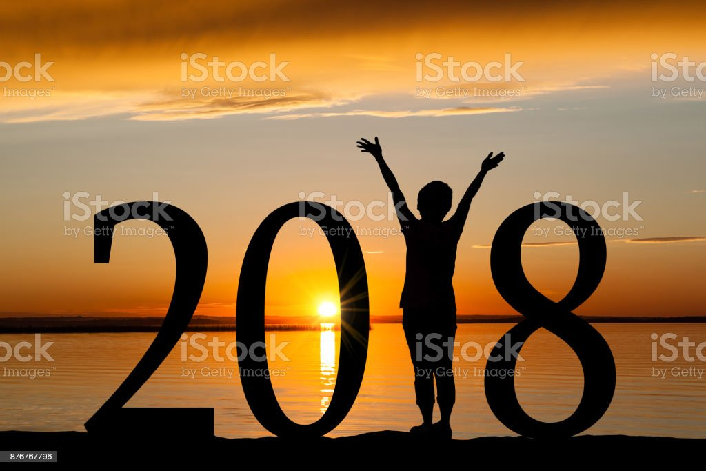 2018 New Year Silhouette of Woman at Golden Sunset stock photo