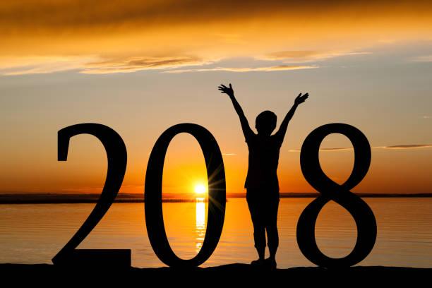 2018 neujahr silhouette der frau am goldenen sonnenuntergang - ideen für silvester stock-fotos und bilder