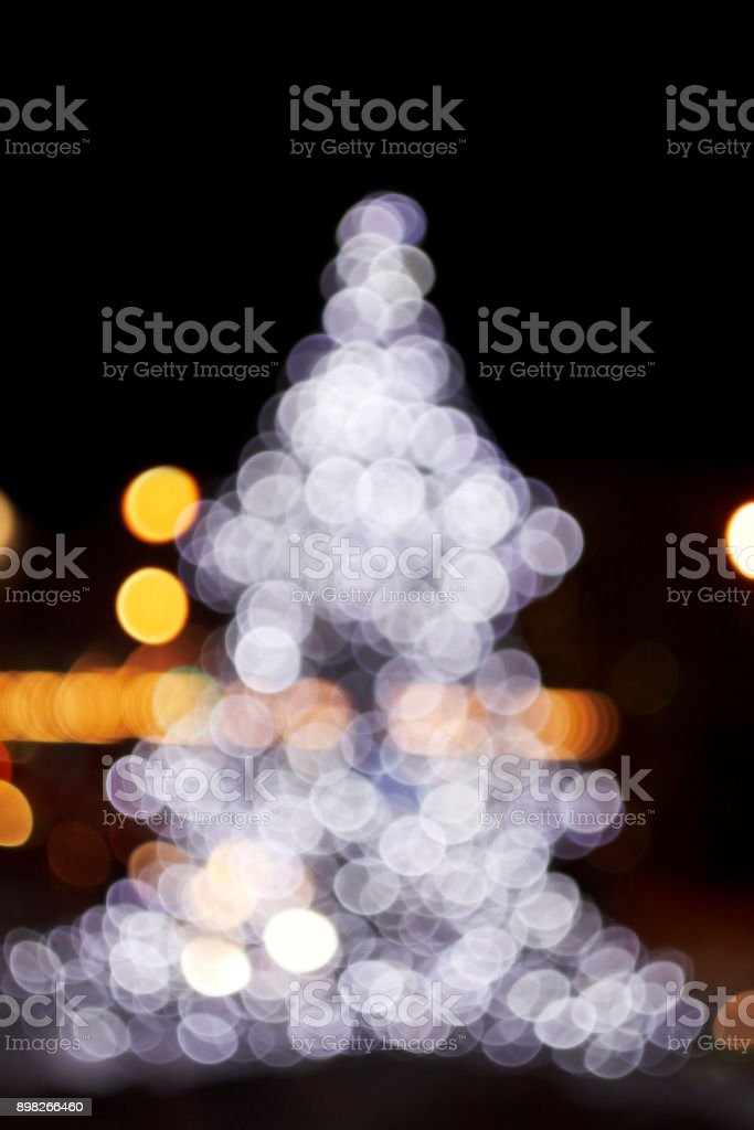 New Year. The Christmas tree. Bright lights. Dark background stock photo