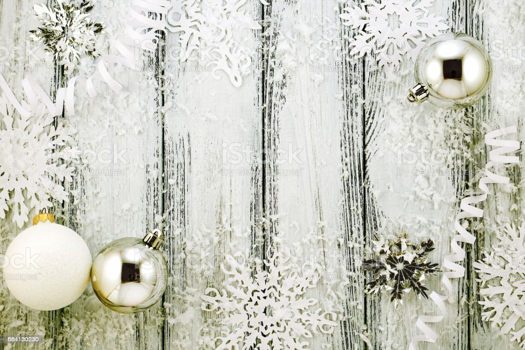 New year theme: Christmas tree white and silver decorations, balls, snow, snowflakes, serpentine on white retro stylized wood background with yellow backlight foto stock royalty-free