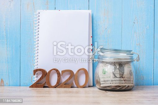 2020 New Year with blank notebook, money glass jar and wooden number. financial, Resolution, Goals, Plan, Action and saving Concept