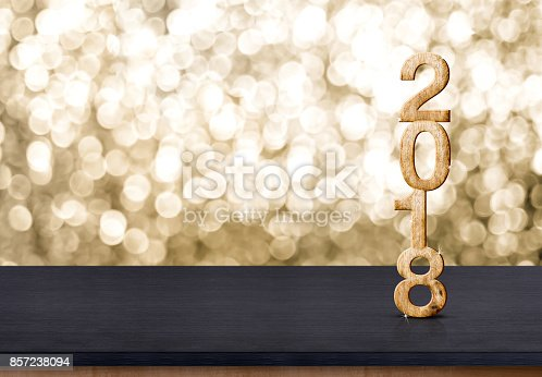 istock 2018 new year wood number on wood table with sparkling gold bokeh wall,panoramic banner for display or montage of product. 857238094