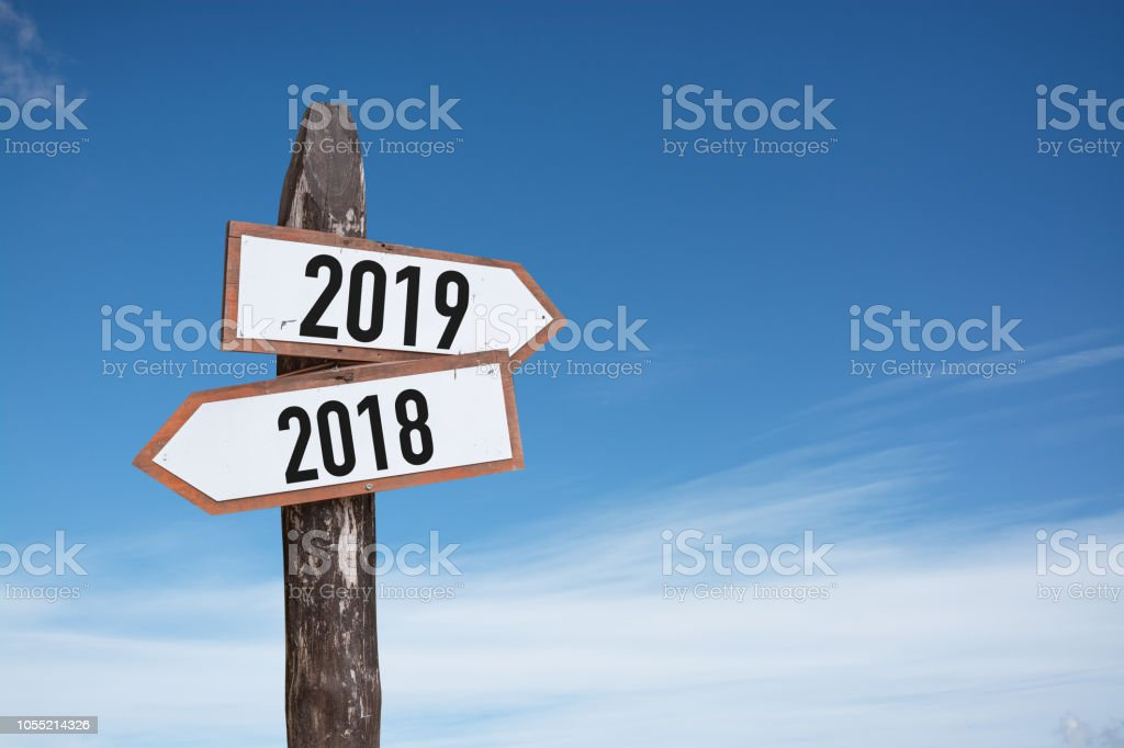 New Year wooden road sign with shining blue sky background. stock photo