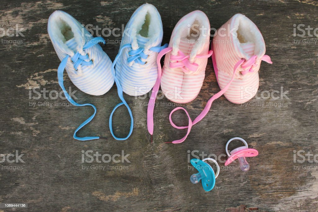 2019 new year written laces of children's shoes and pacifier on old wooden background. Top view. Flat lay. royalty-free stock photo