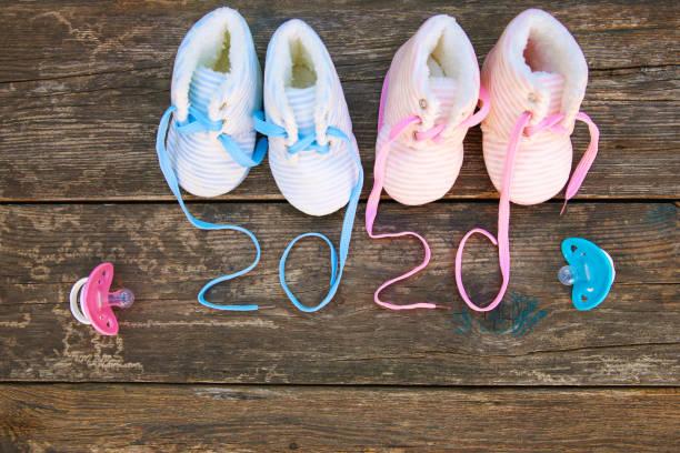 2020 neujahr geschrieben schnürsenkel von kinderschuhen und schnuller auf altem holzhintergrund. ansicht von oben. flach liegen. - babyschuh stock-fotos und bilder