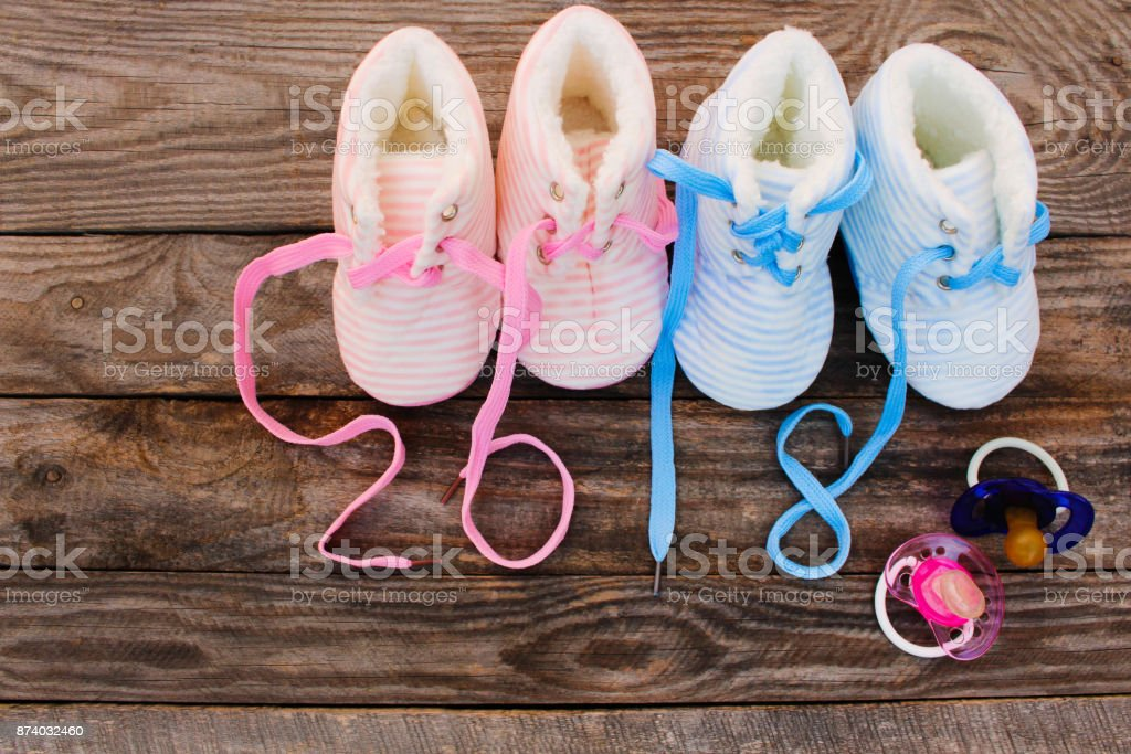 2018 new year written laces of children's shoes and pacifier on old wooden background. Toned image stock photo