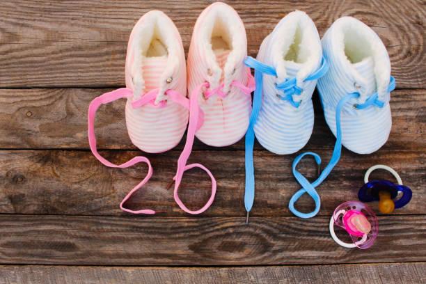 2018 neujahr schnürsenkel der kinderschuhe und schnuller auf alten hölzernen hintergrund geschrieben. getönten bild - kinder winterstiefel stock-fotos und bilder
