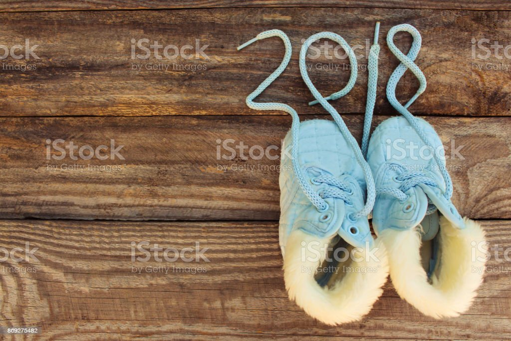 2018 new year written laces of children's shoes on old wooden background. Toned image stock photo