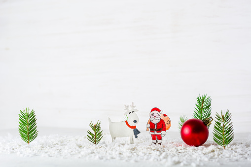 New Year's background. Figures of Santa Claus and deer. Billet for postcards or congratulations. Firs in the forest among the snowdrifts.