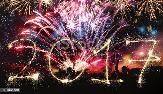 istock new years banner with  colorful fireworks and cheering crowd 621364438