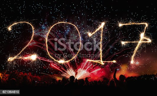 istock 2017 new years banner with  fireworks and cheering crowd 621364610