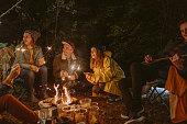 Photo of a group of friends celebrating New Year's by throwing a campfire party in the woods; lightning sparklers while sitting by the campfire, and enjoying each other's company.