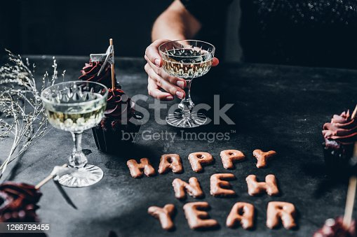 Happy new year cookie on table with cupcakes and a woman sitting holding a glass of champagne.