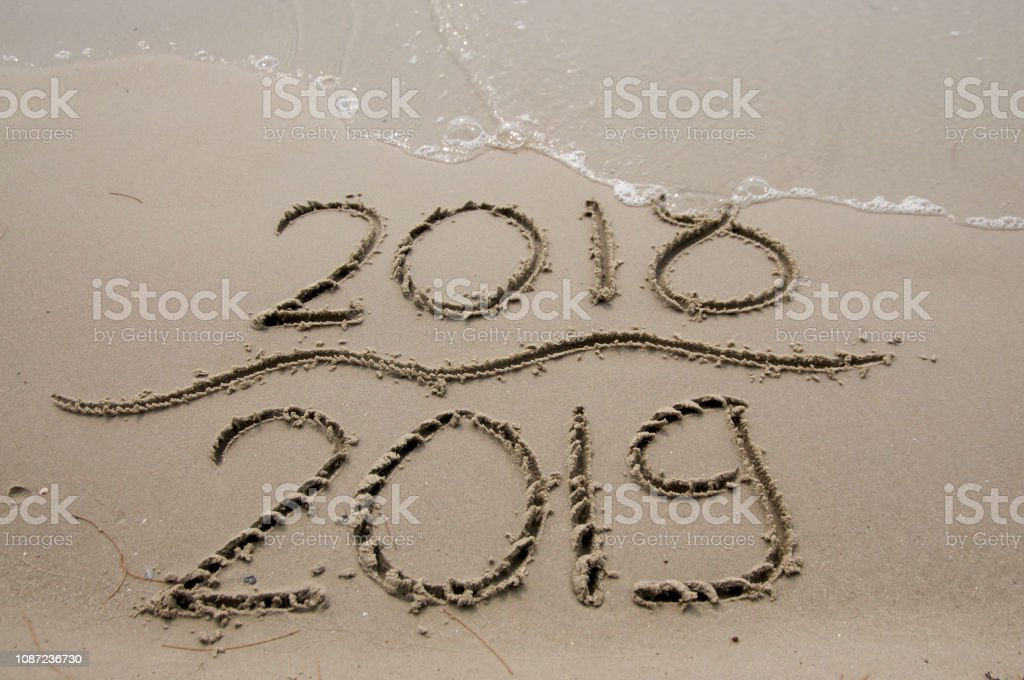 The water erases the 2018 text written on the beach