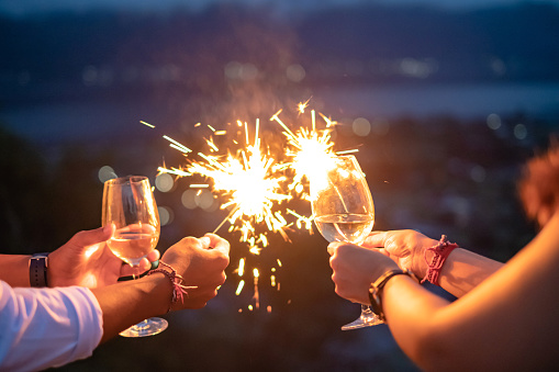 Close up shot of Asian male and female hands holding sparklers and white wine at night time during new year's eve celebration