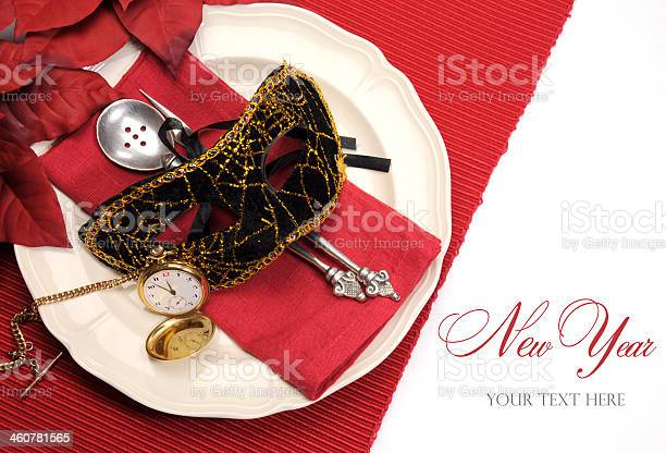 New Years Eve dining table place setting with masquerade mask