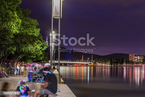 Canberra, Australia - December 31, 2018: Night view of New Year's Eve, Large Group of People watching Fireworks at Lake Burley Griffin in Canberra.