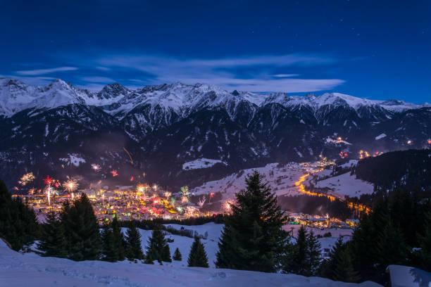 silvester-feuerwerk über dem dorf fiss in österreich mit schneebedeckten bergen und sternen - fiss tirol stock-fotos und bilder