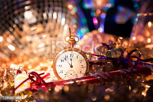 New Year's Even holiday party with lights and candles.  Centerpiece of image is an antique pocket watch with time set at almost midnight.