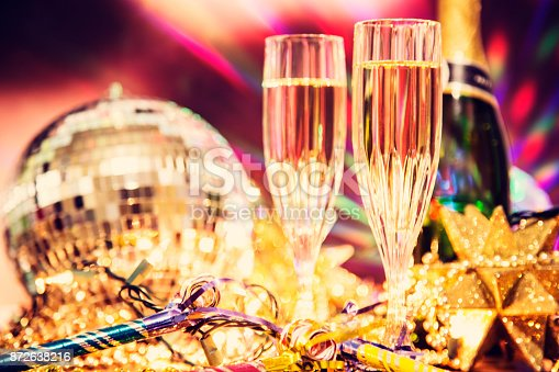 istock New Year's Eve holiday party with champagne, disco ball, decorations. 872638216