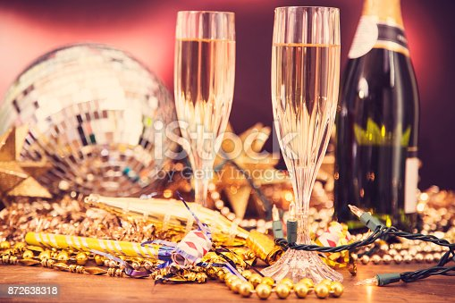 istock New Year's Eve holiday party with champagne, disco ball, decorations. 872638318
