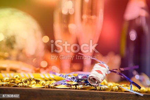 istock New Year's Eve holiday party with champagne, disco ball, decorations. 872638402