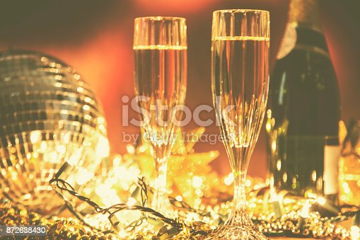 istock New Year's Eve holiday party with champagne, disco ball, decorations. 872638430